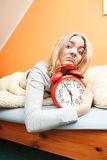 Unhappy woman waking up with alarm clock. Stock Image