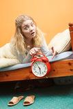 Unhappy woman waking up with alarm clock. Royalty Free Stock Photos