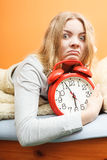Unhappy woman waking up with alarm clock. Stock Images