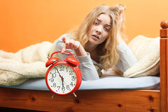 Unhappy woman waking up with alarm clock. Royalty Free Stock Images