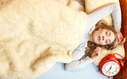 Unhappy woman waking up with alarm clock. Stock Photography