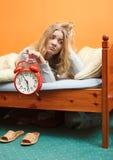Unhappy woman waking up with alarm clock. Stock Photos