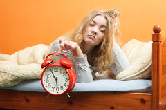 Unhappy woman waking up with alarm clock. Stock Photos