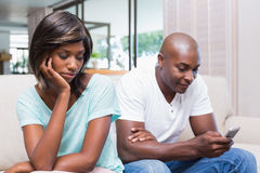 Unhappy woman watching her boyfriend texting Stock Photos