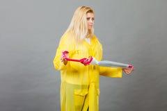 Unhappy woman wearing raincoat holding closed umbrella. Bad mood during rainy day. Unhappy blonde woman wearing yellow raincoat holding closed umbrella Stock Photos