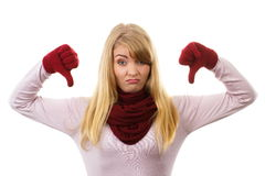 Unhappy woman in woolen gloves showing thumbs down, negative emotions Royalty Free Stock Photography