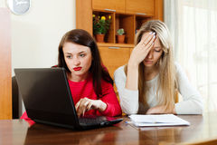 Unhappy women looking  documents with laptop Royalty Free Stock Image