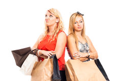 Unhappy women shopping. Two young blond unhappy women holding shopping bags, isolated on white background Stock Photo