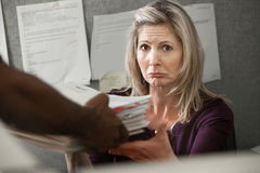 Unhappy Worker. Unhappy Caucasian worker given a stack of files at a cubicle stock image