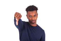 Unhappy young african american man making thumbs down gesture is Stock Photo