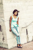 Unhappy young African American woman thinking outside in New Yor. Unhappy Girl. Young pretty woman wearing green tank top, drop earrings, blue fashionable jeans Stock Photography