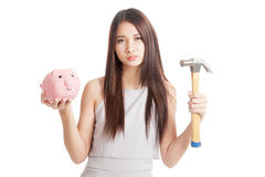 Unhappy  young Asian woman with piggy bank and hammer Royalty Free Stock Photo