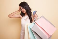 Unhappy young Asian woman with shopping bags and credit card. Unhappy young Asian woman with shopping bags and credit card on beige background stock image