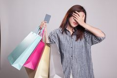 Unhappy young Asian woman with shopping bags and credit card. Unhappy young Asian woman with shopping bags and credit card on gray background stock image