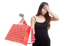 Unhappy  young Asian woman with shopping bags and credit card.. Unhappy  young Asian woman with shopping bags and credit card isolated on white background Royalty Free Stock Images