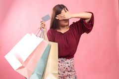 Unhappy  young Asian woman with shopping bags and credit card. On pink background stock images