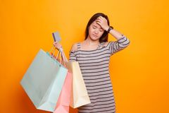 Unhappy  young Asian woman with shopping bags and credit card. Unhappy  young Asian woman with shopping bags and credit card on yellow background Royalty Free Stock Photo