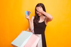 Unhappy young Asian woman with shopping bags and credit card. Unhappy young Asian woman with shopping bags and credit card on yellow background stock photo