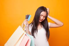 Unhappy young Asian woman with shopping bags and credit card. Unhappy young Asian woman with shopping bags and credit card on bright yellow background royalty free stock photography