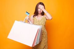 Unhappy young Asian woman with shopping bags and credit card. Unhappy young Asian woman with shopping bags and credit card on yellow background royalty free stock images