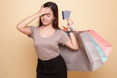 Unhappy  young Asian woman with shopping bags and credit card. Unhappy  young Asian woman with shopping bags and credit card on beige background Stock Images