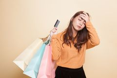 Unhappy  young Asian woman with shopping bags and credit card. Unhappy  young Asian woman with shopping bags and credit card on beige background Royalty Free Stock Images