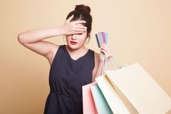 Unhappy young Asian woman with shopping bags and credit card. Unhappy young Asian woman with shopping bags and credit card on beige background royalty free stock photos