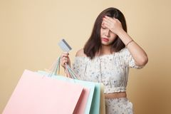 Unhappy young Asian woman with shopping bags and credit card. Unhappy young Asian woman with shopping bags and credit card on beige background stock photo