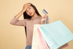 Unhappy  young Asian woman with shopping bags and credit card. On beige background stock image