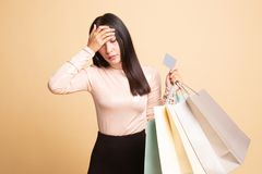Unhappy  young Asian woman with shopping bags and credit card. On  beige background royalty free stock photography