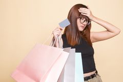 Unhappy  young Asian woman with shopping bags and credit card. On beige background royalty free stock images