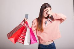 Unhappy  young Asian woman with shopping bags and credit card. Unhappy  young Asian woman with shopping bags and credit card on gray background Royalty Free Stock Photography