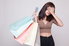 Unhappy  young Asian woman with shopping bags and credit card. Unhappy  young Asian woman with shopping bags and credit card on gray background Royalty Free Stock Image