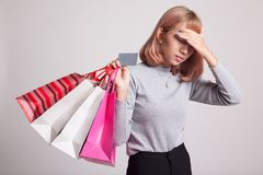 Unhappy young Asian woman with shopping bags and credit card. Unhappy young Asian woman with shopping bags and credit card on gray background stock photography