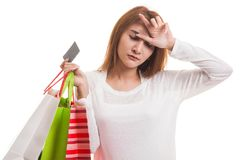 Unhappy  young Asian woman with shopping bags and credit card. Unhappy  young Asian woman with shopping bags and credit card  isolated on white background Royalty Free Stock Photography