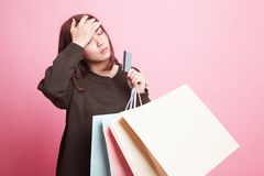 Unhappy  young Asian woman with shopping bags and credit card. Unhappy  young Asian woman with shopping bags and credit card on pink background Royalty Free Stock Photos