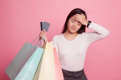 Unhappy  young Asian woman with shopping bags and credit card. Unhappy  young Asian woman with shopping bags and credit card on pink background Stock Photo