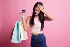 Unhappy young Asian woman with shopping bags and credit card. Unhappy young Asian woman with shopping bags and credit card on pink background stock image