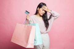 Unhappy young Asian woman with shopping bags and credit card. Unhappy young Asian woman with shopping bags and credit card on pink background royalty free stock photography
