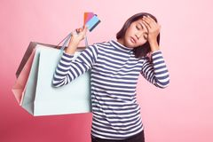 Unhappy young Asian woman with shopping bags and credit card. Unhappy young Asian woman with shopping bags and credit card on pink background royalty free stock images