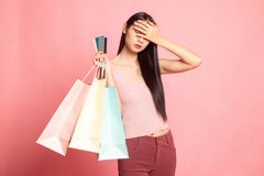 Unhappy young Asian woman with shopping bags and credit card. On pink background royalty free stock photo