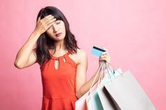 Unhappy young Asian woman with shopping bags and credit card. On pink background stock photography