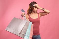 Unhappy  young Asian woman with shopping bags and credit card. On pink background stock photos