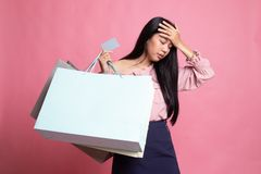 Unhappy  young Asian woman with shopping bags and credit card. On pink background royalty free stock photos
