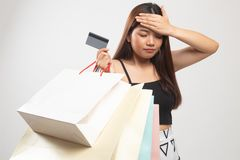Unhappy  young Asian woman with shopping bags and credit card. On white background stock photo