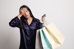 Unhappy  young Asian woman with shopping bags and credit card. On white background stock photos