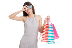Unhappy  young Asian woman with shopping bags and credit card. On white background Stock Images