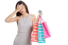 Unhappy  young Asian woman with shopping bags and credit card. On white background Stock Image