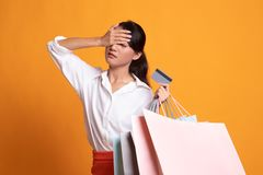Unhappy  young Asian woman with shopping bags and credit card. On yellow background royalty free stock photos