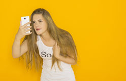 Unhappy young attractive woman very surprised something on her smartphone. Funny girl with mobile phone reads message. Studio shot orange background Stock Photography